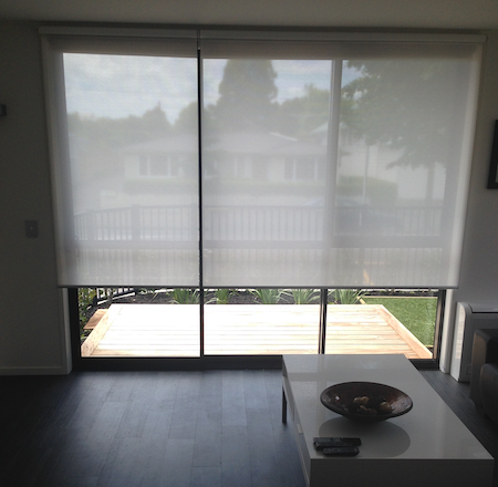 sunscreen blinds over a sliding door in a homes lounge area